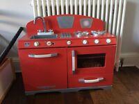 Red, wooden toy kitchen.