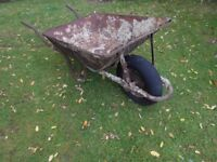 A used classic rusty wheelbarrow with pumped up tyre