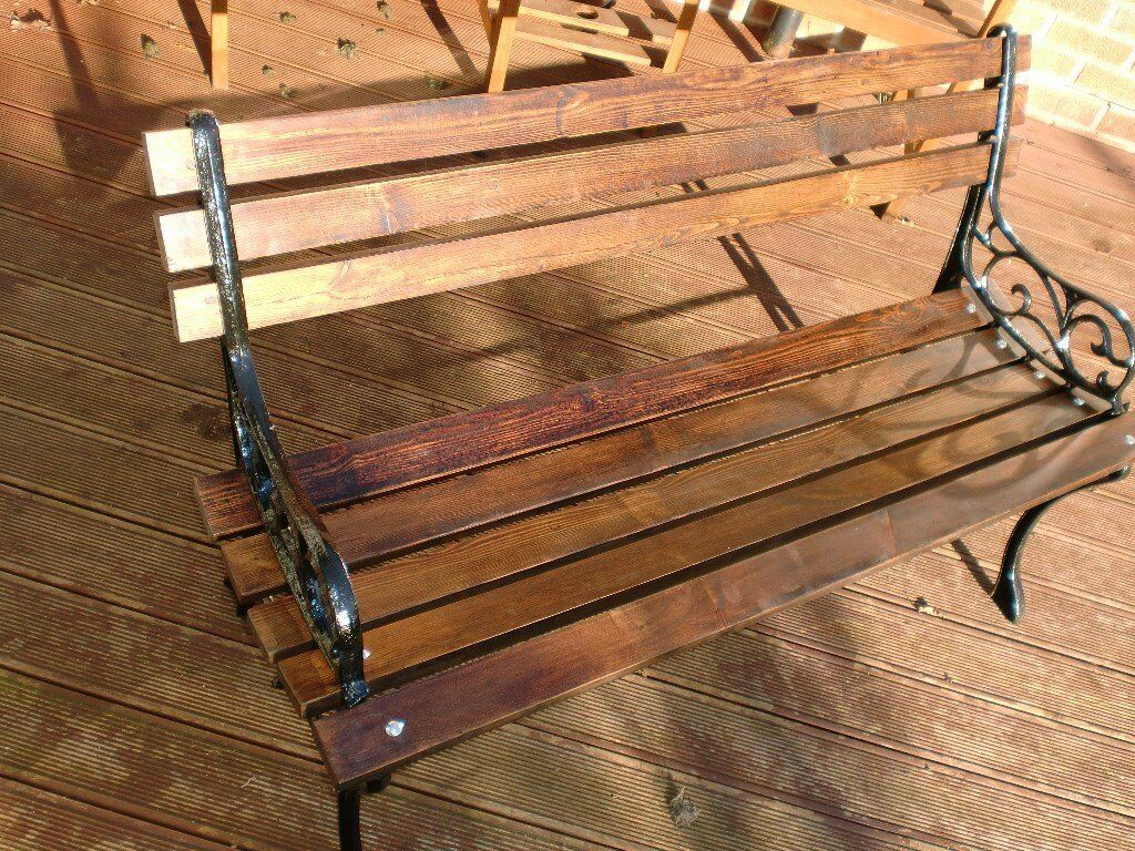 A Refurbished Cast Iron Garden Bench With Stained And Polished Wooden Slats