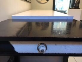 Dark brown wooden table with cow print drawer
