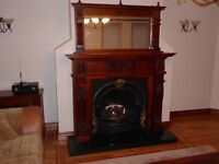 Solid oak fireplace with matching oak mirror. Includes cast iron inset and black granite hearth