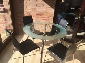 Glass round dining table with black leather chairs