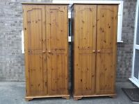 Two pine wardrobes with two opening doors.
