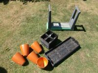 5 flower pots . stack of seed trays and a kneeling stool