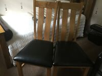 Two oak chairs with black leather seats