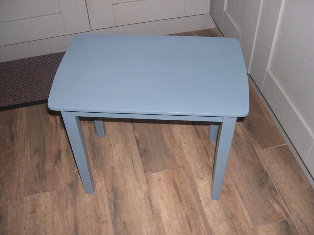 A small wooden table painted in a bluish grey colour.
