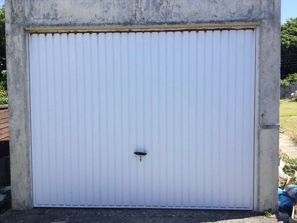 White Garage Door For Single Garage Has A Lock With Keys In