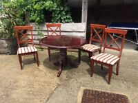 4xHigh backed wooden chairs with padded seats. They come with a round table in the same style/wood.