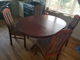 Extending wood dining table plus four material covered chairs. 4'9 x 3'6 fully extended.