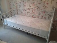 A single white metal day bed (mattress not included)