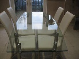 Glass dining table with four ivory faux leather chairs, will extend to seat six.