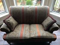 Two textile sofas with matching cushions and wooden legs. Traditional country house Victorian style