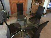 Glass circular dining table and 4 faux leather chairs.