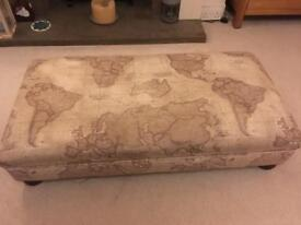 Large footstool upholstered in John Lewis word map fabric.