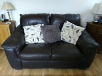 Pair of brown leather two seater sofas.
