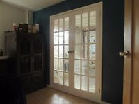 Pair of internal wooden doors, glazed, with white painted finish.