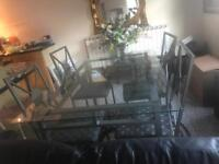 Glass top dining table and four chairs with metal frame
