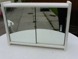 WHITE WOODEN PAINTED CABINET WITH SLIDING MIRROR DOORS. 50 X 13 X 36 CMS., WITH SHELF INSIDE