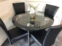 Glass dining table with 4 black leather chairs