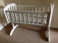 White baby swinging crib with mattress.