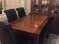 Wooden dining table with leather chairs