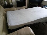 Two seater cream leather sofa bed with spring mechanism for easy pull out. Good condition.
