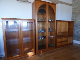 Teak display unit comprising three cabinets with glass doors and internal lighting.