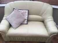 Cream leather two seater and chair.