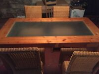 Large wooden dining table with glass top insert and 4 wicker chairs.