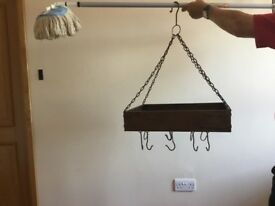 A brown cast iron hanging ceiling rack for kitchen utensils etc with hooks
