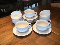 Six white cups and saucers.