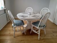 White round extending dining table and four chairs painted