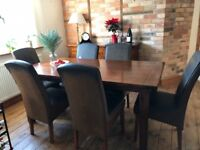 Solid acacia wood dining room table and six leather look high-back chairs in great used condition