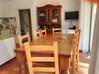 Large Pine Dining Table with 8 wooden chairs.