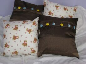 "Pair of 14"" brown cushions with button opening."