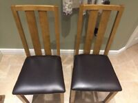 2 oak effect dining chairs with brown leather padded seat