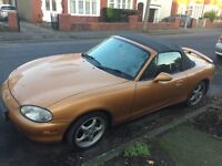 Bronze/gold Mazda Convertable