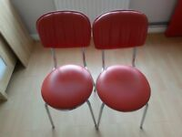 2 metal framed chairs with red leather cover seats