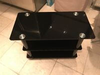 Tv stand black glass. Excellent condition 70cm by 35cm £30 NO OFFERS.CAN DELIVER