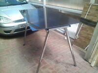 big black glass table with that are adjustable legs