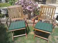 Two hardwood garden chairs with cushions