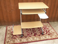 A computer desk, with slide out section and a swivel out cup tray.