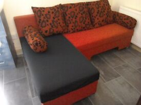 Red and black corner sofa bed with storage
