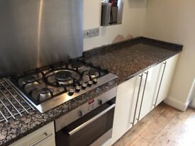 Kitchen units, granite worktop, electric oven, gas hob, stainless sink.