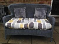 Grey painted wicker sofa with cushions. 2 seater