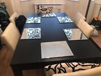 Black dining table and 6 faux cream chairs
