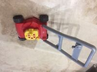 Toy lawnmower with clicking ear lever and pull starter.