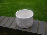 A white ceramic planter with attractive outer surface.