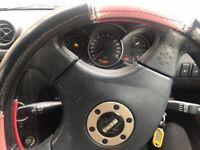 Black Daihatsu Copen. Red leather interior.