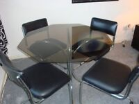 Glass Table and 4 Chrome and Black Cushioned Chairs